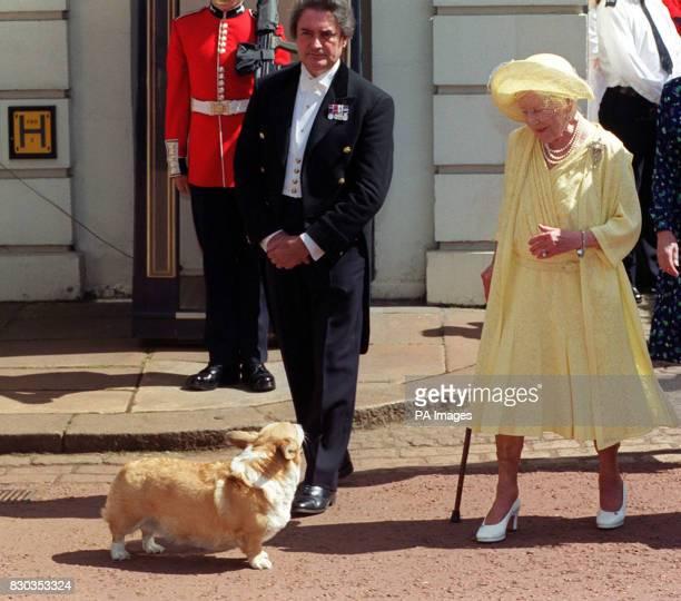 File picture dated 4/8/99 of Britain's Queen Elizabeth the Queen Mother admiring one of her corgis Her daughter Queen Elizabeth II told cystic...