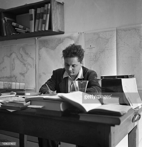 File picture dated April 1952 of French biologist and physician Alain Bombard working at his desk. Alain Bombard sailed across the Atlantic Ocean...