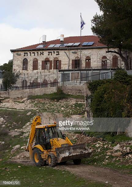 File picture dated January 5 2010 shows a Palestinian worker driving his tractor next to the Jewish settlement of Bet Orot in the mostly Arab east...