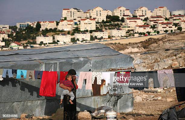 -- File picture dated May 29, 2007 shows a bedouin from the Jahalin tribe carrying her babygirl next to hanging laundry outside her hut near the...