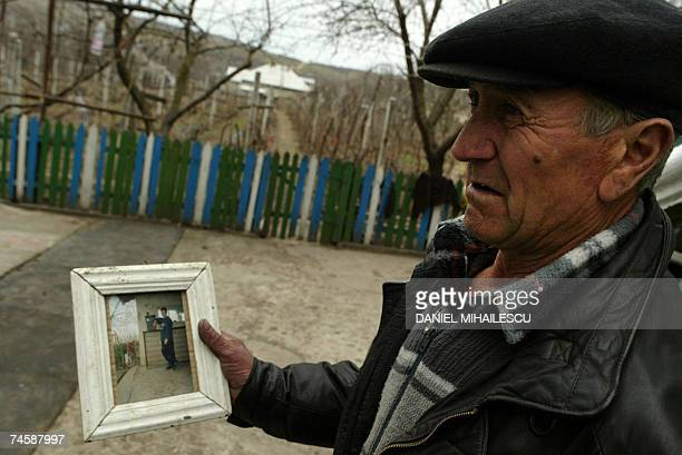 File picture of a 24 years old young man who died one year after he sold his kidney is shown by his father Vasile Dimineti in the village of Mingir...