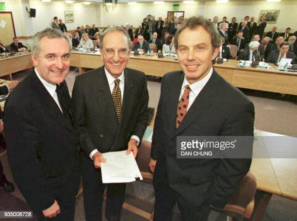 File picture of British Prime Minister Tony Blair US Senator George Mitchell and Irish Prime Minister Bertie Ahern smiling on April 10 after they...