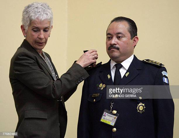 File picture of Guatemalan Minister of Government Adela de Torrebiarte pinning the epaulets to General Director of the National Police Julio...