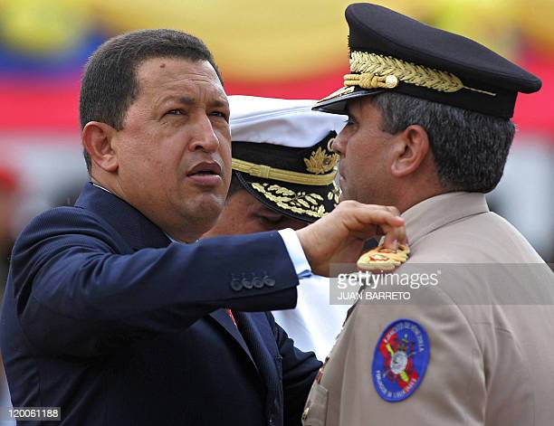 File picture of Venezuelan President Hugo Chavez and outgoing Minister of Defense Orlando Maniglia as he decorates incoming Minister of Defense...