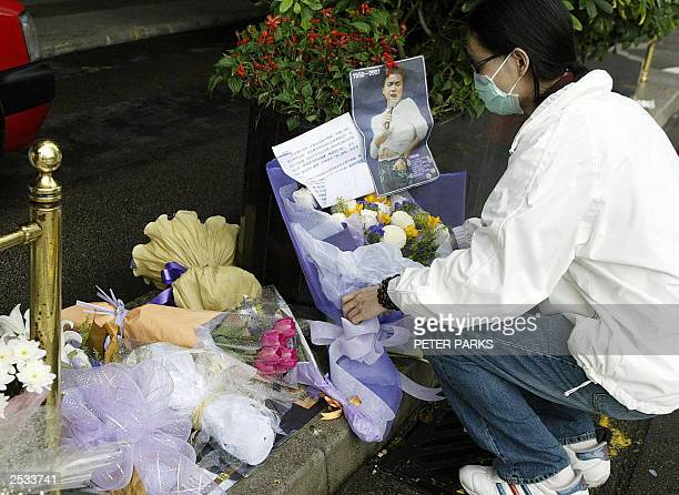 File picture taken 02 April 2003 shows a fan of Cantopop singer and actor Leslie Cheung placing flowers and a message outside the Mandarin Hotel in...
