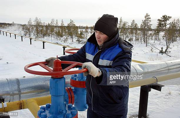 File picture taken 02 November 2006 shows a worker as he opens a valve of a gas pipeline of the Russian Gazprom enterprise in Vyngayakhinsky gas...