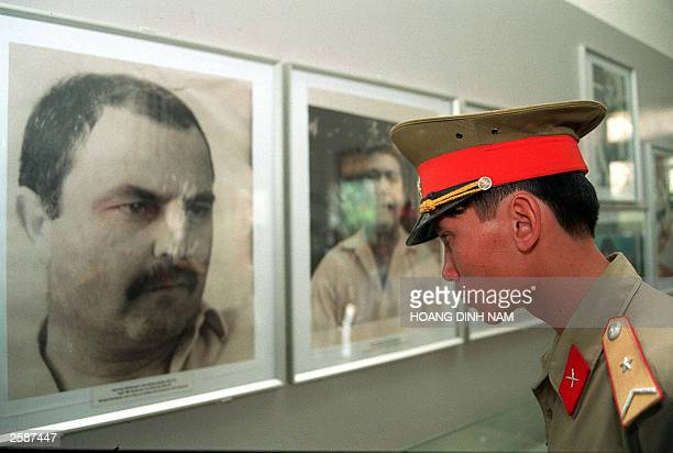 US File picture taken 15 March 1998 shows a Vietnamese soldier looking at a portrait of Michael Bernhard a US GI who took part in the My Lai massacre...