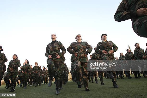 A file picture taken on January 21 shows a women from the Syrian National Defense force parade at their training center in Wadi alDahab in the Syrian...
