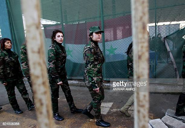 A file picture taken on January 21 shows women from the Syrian National Defense force who just finished training walking in file at a training center...