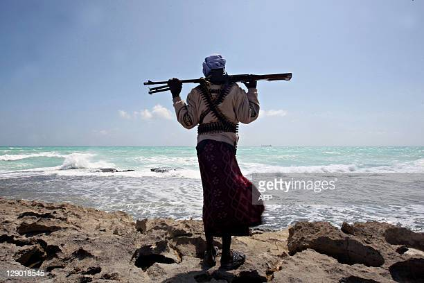 A file picture taken on January 7 2010 shows an armed Somali pirate along the coastline while the Greek cargo ship MV Filitsa is seen anchored just...