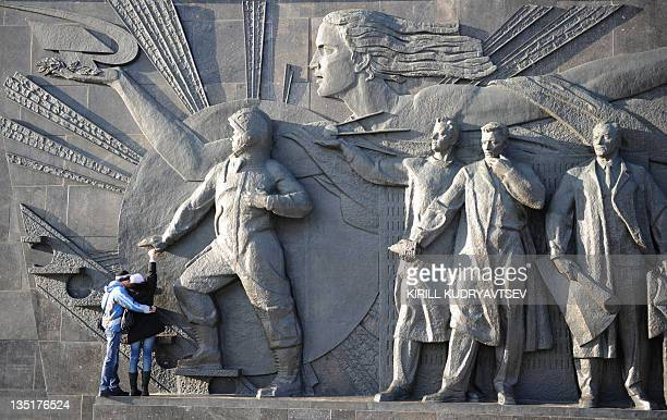 A file picture taken on November 20 shows a couple looking at 'To Conquerors of Space' basrelief on a wall of the Cosmonautics Memorial Museum in...