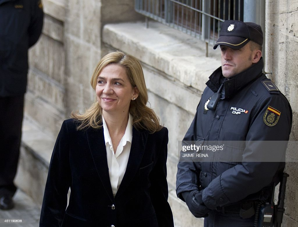 A file picture takenon February 8, 2014 shows Spanish Infanta Cristina (L) smiling as she arrives at the courthouse of Palma de Mallorca, on the Spanish Balearic Island of Mallorca. A Spanish judge ruled on June 25 that King Felipe VI's sister, Princess Cristina, and her husband must face fraud charges, opening the way to an unprecedented criminal trial. Less than a week after Felipe, 46, took the Spanish throne promising an 'honest and transparent' monarchy, the ruling refocused attention on a scandal that had blighted the reign of his 76-year-old father Juan Carlos.