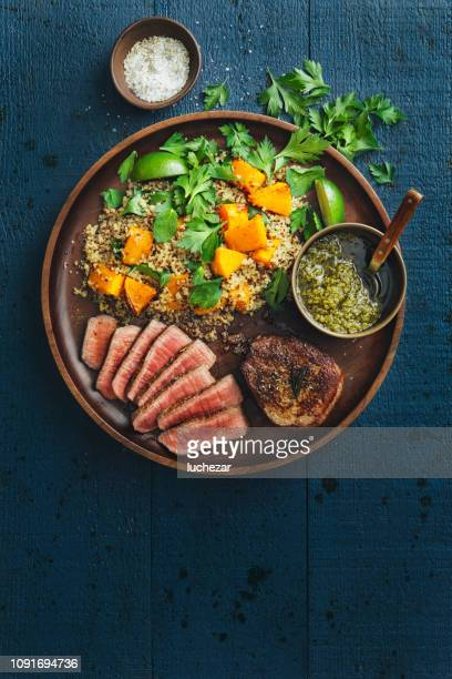 filet mignon with chimichurri and quinoa salad with caramelised and mashed pumpkin - carne de churrasco imagens e fotografias de stock
