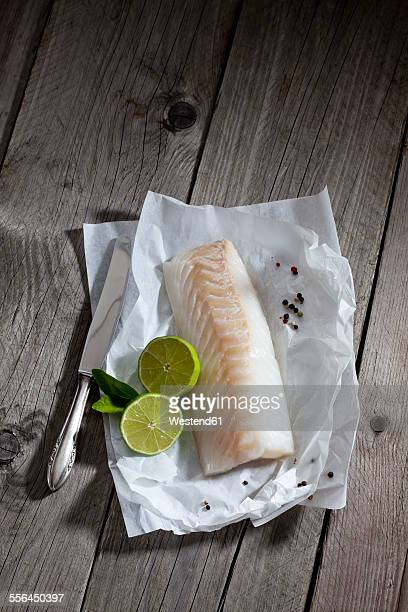 filet of codfisch, lime and knife, and peppercorns on greaseproof paper on wood - fillet stock pictures, royalty-free photos & images