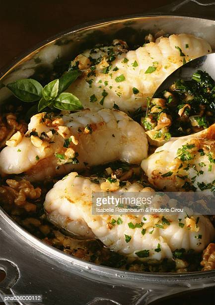 Filets of monkfish in dish with herbs, close-up