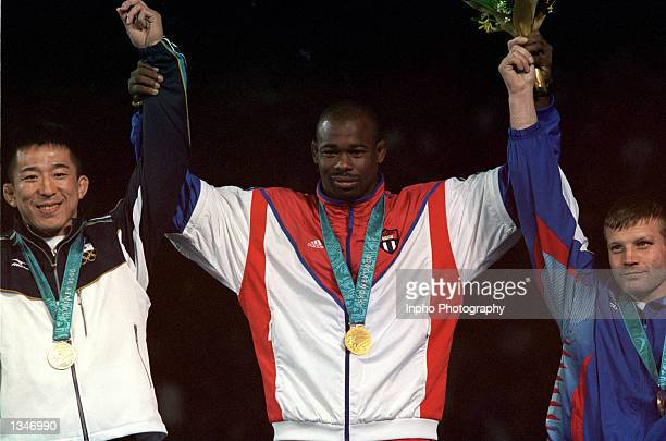 Filiberto Azcuy of Cuba receives his gold medal celebrates with silver medalist Katsuhiko Nagata of Japan and bronze medalist Alexei Glouchkov of...