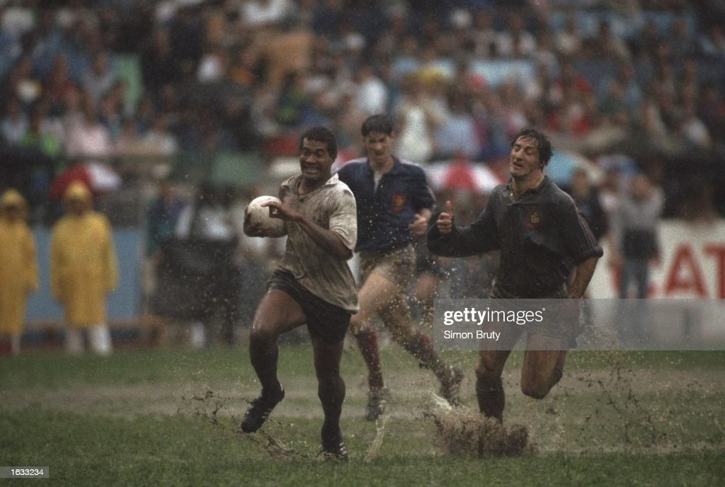Filimone Seru of Fiji powers forwards as he is chased through the mud and rain by Philippe Sella : News Photo