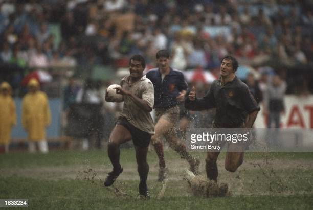 Filimone Seru of Fiji powers forwards as he is chased through the mud and rain by Philippe Sella of France during the Hong Kong Sevens in Hong Kong...