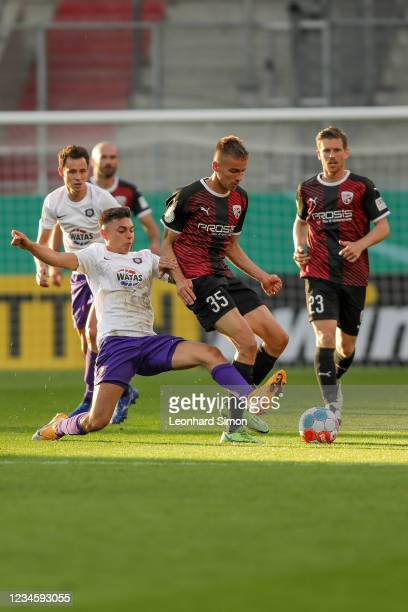 Filip Bilbija of FC Ingolstadt 04 and players of Erzgebirge Aue in action during the DFB Cup first round match between FC Ingolstadt 04 and...