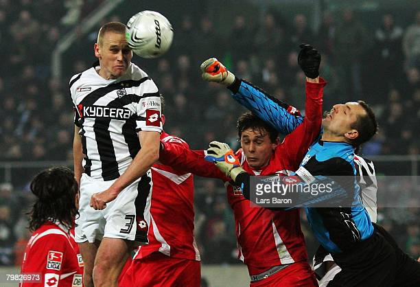 Filip Daems of Moenchengladbach goes for a header with Neven Subotic while goalkeeper Daniel Ischdonat of Mainz defends during the 2nd Bundesliga...