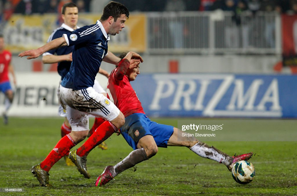 Filip Djuricic (R) of Serbia is challenged by Grant Hanley (L) of Scotland during the FIFA 2014 World Cup Qualifier between Serbia and Scotland at Karadjordje Stadium on March 26, 2013 in Novi Sad, Serbia