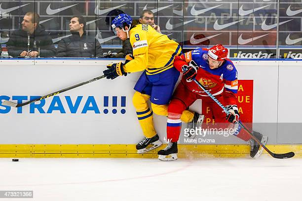 Filip Forsberg of Sweden and Nikolai Kulyomin of Russia battle for the puck during the IIHF World Championship quaterfinal match between Sweden and...