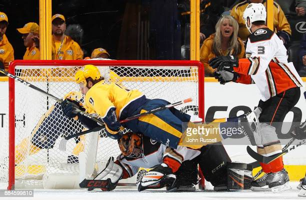 Filip Forsberg of the Nashville Predators collides with goalie Ryan Miller of the Anaheim Ducks during an NHL game at Bridgestone Arena on December 2...