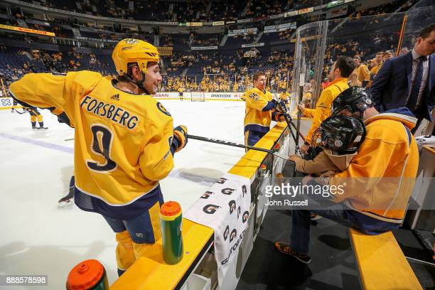 Filip Forsberg of the Nashville Predators serves up a puck for a young fan during warmups prior to an NHL game at Bridgestone Arena on December 8...