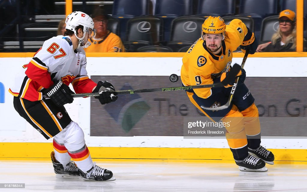 Filip Forsberg #9 of the Nashville Predators tries to control a bouncing puck in front of Michael Frolik #67 of the Calgary Flames during the first period at Bridgestone Arena on February 15, 2018 in Nashville, Tennessee.