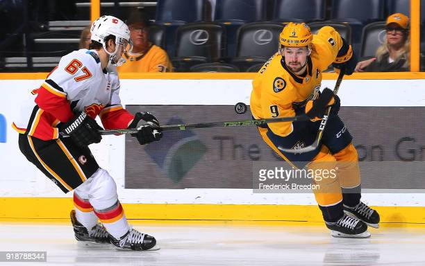 Filip Forsberg of the Nashville Predators tries to control a bouncing puck in front of Michael Frolik of the Calgary Flames during the first period...