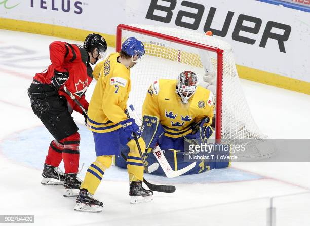 Filip Gustavsson of Sweden makes a save with Boris Katchouk of Canada and Timothy Liljegren of Sweden looking for a rebound during the second period...