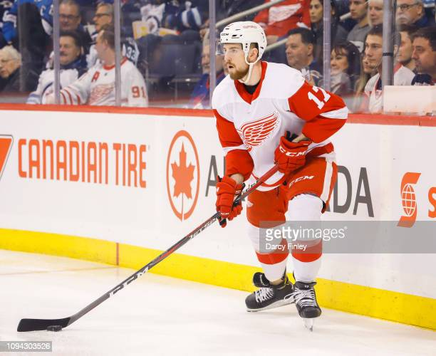 Filip Hronek of the Detroit Red Wings plays the puck along the boards during first period action against the Winnipeg Jets at the Bell MTS Place on...