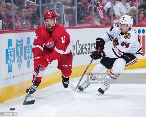 Filip Hronek of the Detroit Red Wings skates with the puck behind the net followed by Alexandre Fortin of the Chicago Blackhawks during a pre-season...