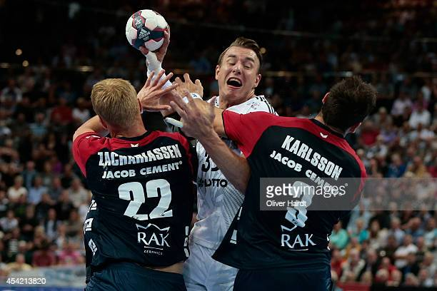 Filip Jicha of Kiel challenges for the ball with Anders Zachariassen and Tobias Karlsson of Flensburg during the DKB HBL Bundesliga match between THW...