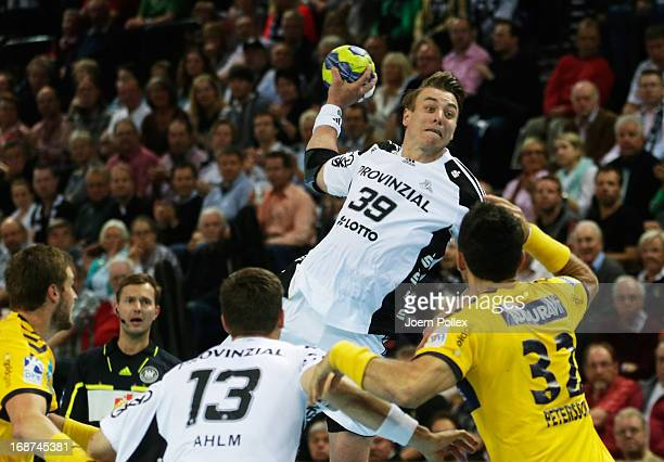 Filip Jicha of Kiel is challenged by Alexander Petersson of RheinNeckar Loewen during the DKB Handball Bundesliga match between THW Kiel and Fuechse...