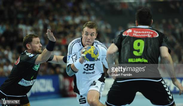 Filip Jicha of Kiel is challenged by Jon Hannes Jonsson and Asgeir Orn Hallgrimsson of Hannover during the Toyota handball Bundesliga match between...