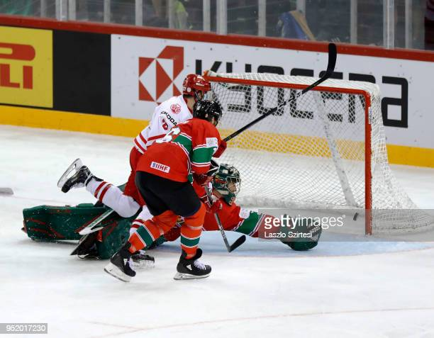Filip Komorski of Poland scores next to Bence Sziranyi of Hungary and goalie Adam Vay of Hungary during the 2018 IIHF Ice Hockey World Championship...