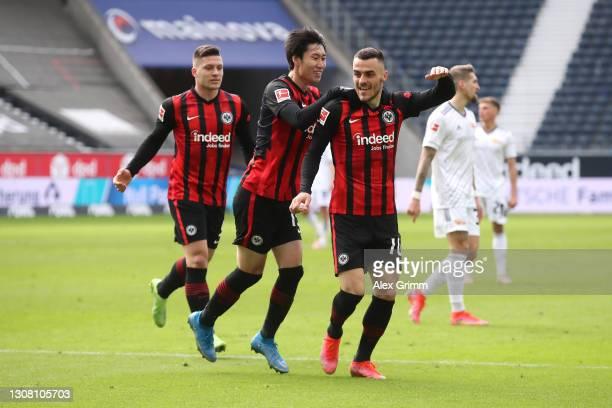 Filip Kostic of Eintracht Frankfurt celebrates with Daichi Kamada and Luka Jovic after scoring their team's third goal during the Bundesliga match...