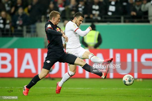 Filip Kostic of Eintracht Frankfurt scores his sides fifth goal past Lukas Klostermann of RB Leipzig during the DFB Cup round of sixteen match...