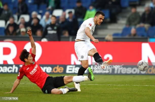 Filip Kostic of Eintracht Frankfurt scores his team's third goal under pressure from Genki Haraguchi of Hannover 96 during the Bundesliga match...