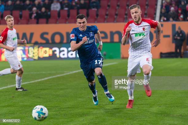 Filip Kostic of Hamburg and Jeffrey Gouweleeuw of Augsburg battle for the ball during the Bundesliga match between FC Augsburg and Hamburger SV at...