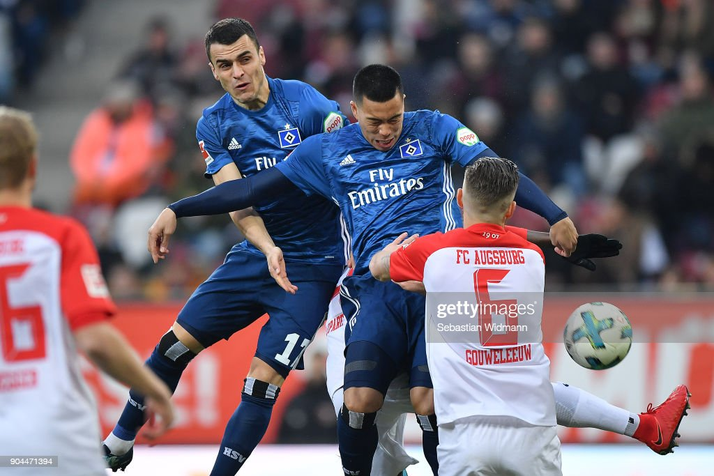 Filip Kostic of Hamburg, Bobby Wood of Hamburg and Jeffrey Gouweleeuw of Augsburg fight for the ball during the Bundesliga match between FC Augsburg and Hamburger SV at WWK-Arena on January 13, 2018 in Augsburg, Germany.