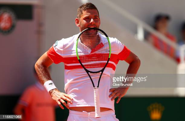 Filip Krajinovic of Serbia bites his racket during his mens singles third round match against Stefanos Tsitsipas of Greece during Day seven of the...