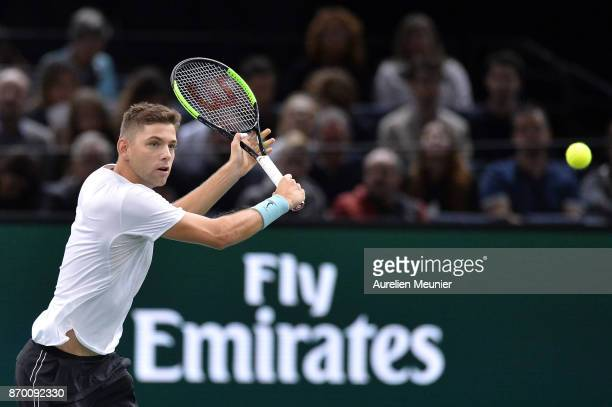 Filip Krajinovic of Serbia plays a backhand in the men's singles semi final match against John Isner of the United States of America during day six...