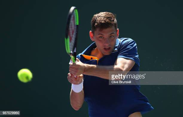 Filip Krajinovic of Serbia plays a forehand against Liam Broady of Great Britain in their second round match during the Miami Open Presented by Itau...