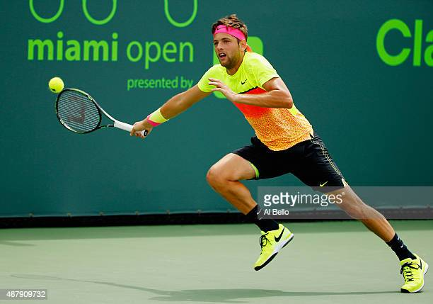 Filip Krajinovic of Serbia returns the ball against Gael Monfils of France during day 6 of the Miami Open at Crandon Park Tennis Center on March 28...