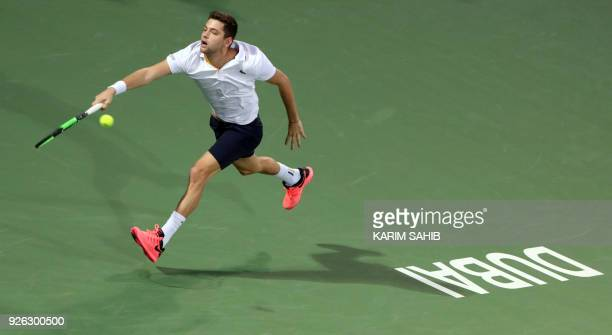 Filip Krajinovic of Serbia returns the ball to Lucas Pouille of France during their semifinal match in the 2018 ATP Dubai Duty Free Tennis...
