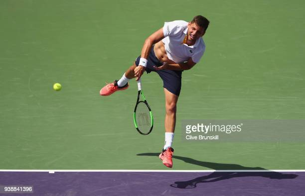 Filip Krajinovic of Serbia serves against Juan Martin Del Potro of Argentina in their fourth round match during the Miami Open Presented by Itau at...