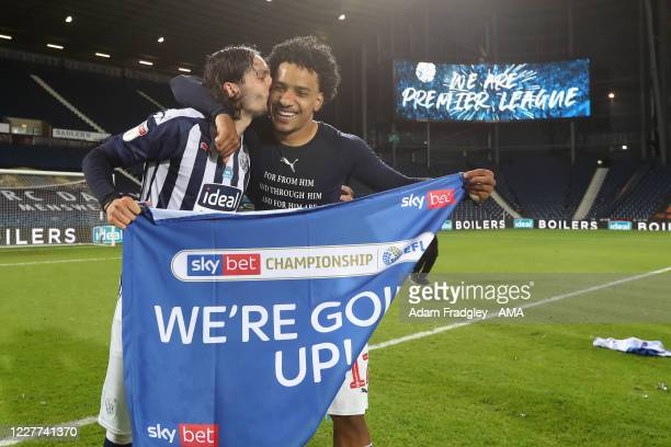 Filip Krovinovic kisses Matheus Pereira of West Bromwich Albion as they celebrate promotion to the Premier League on the pitch at the end of the Sky...