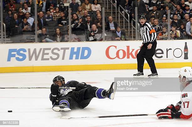 Filip Kuba of the Ottawa Senators falls to the ice with Wayne Simmonds of the Los Angeles Kings defending the puck during the game on December 3,...